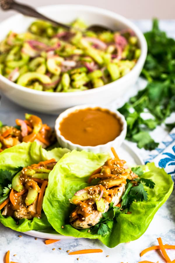 Asian lettuce wraps on a place with cucumber salad behind it.