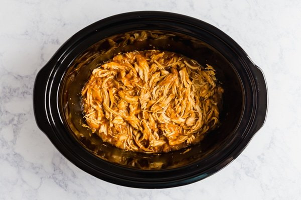Tropical chicken in a slow cooker pot from overhead.