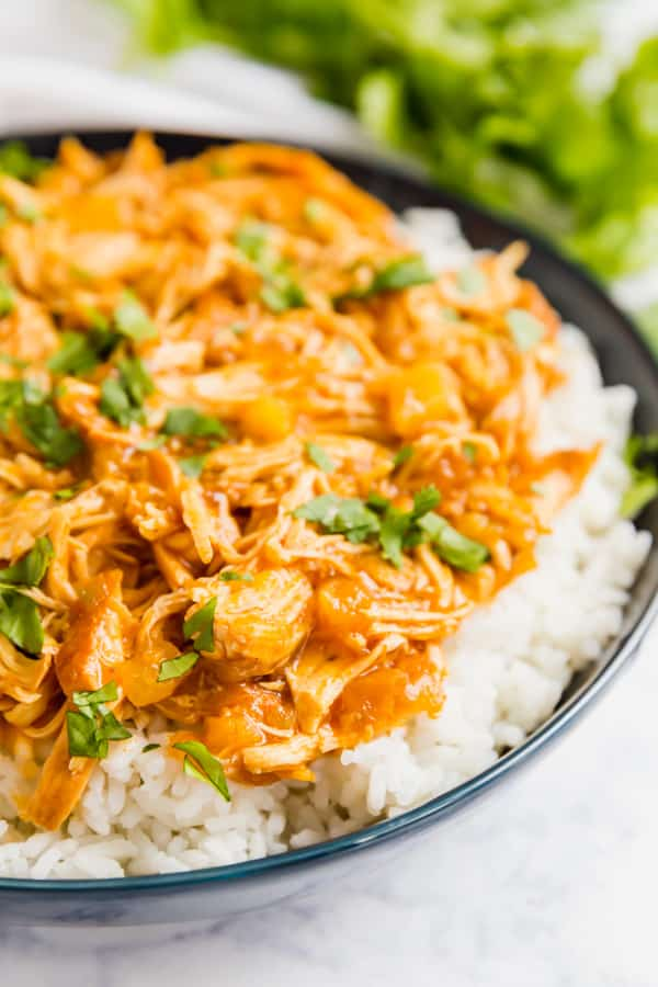 A close up of a bowl of this pineapple chicken recipe over rice.