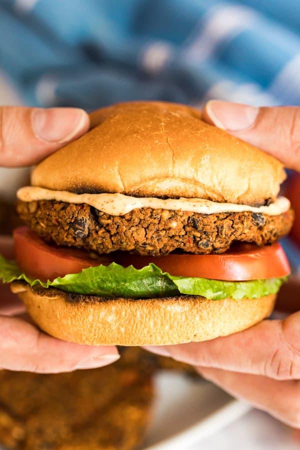Hands holding a black bean burger on a bun.