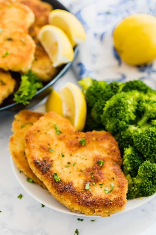A plate with breaded pork chops and broccoli on it.