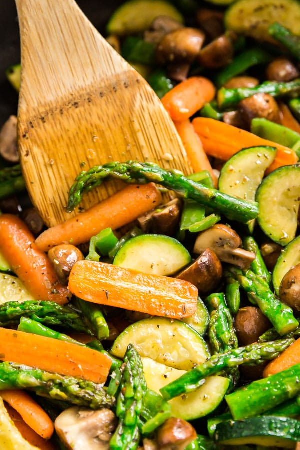 A close up inside of a pan of a bowl of vegetable medley with a wooden spoon in it..