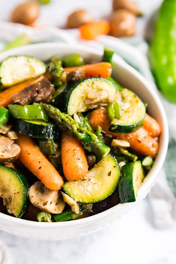 A close up image of stir fry vegetables in a white bowl with raw veggies in the background.