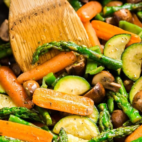 A square image of a close up inside of a pan of a bowl of vegetable medley with a wooden spoon in it.