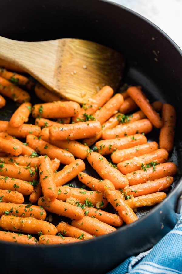 A shot of a saute pan with sautéed carrots.