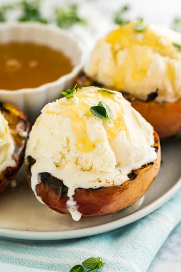 A grilled peach with ice cream melting on top of it.