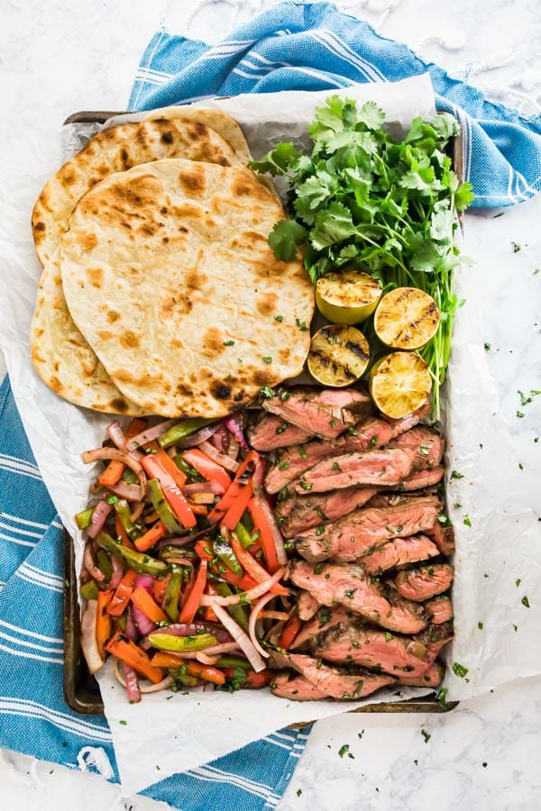 An overhead image of a sheet pan qwith grilled steak fajitas, peppers, onions, tortillas and fresh cilantro.