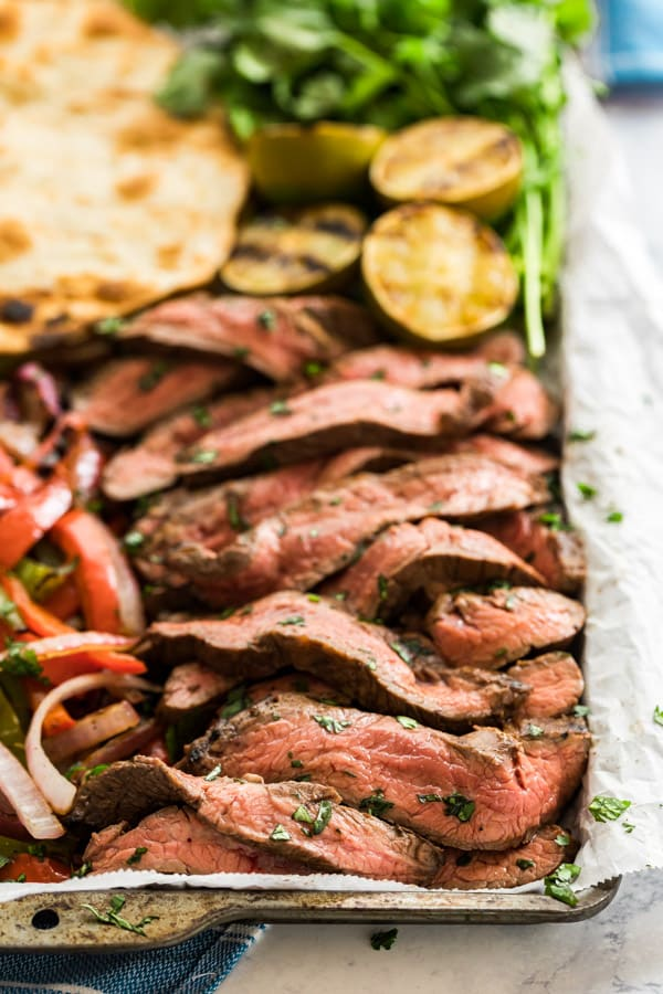 flank steak sliced up on a pan for fajitas
