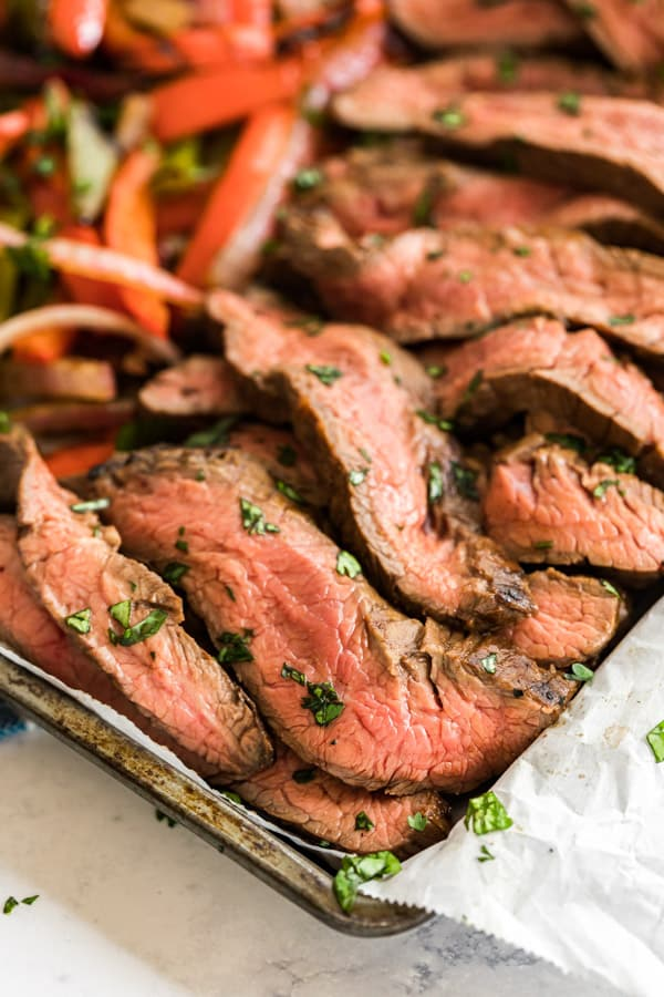 The side of a pan containing the flank steak used for this steak fajitas recipe