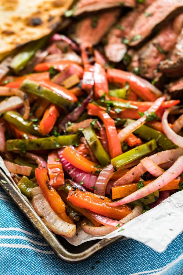 The peppers and onions on a pan used to serve with beef fajitas