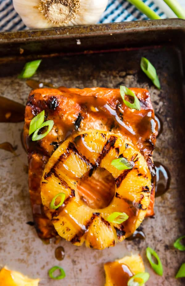An image of salmon that's beein grilled with pineapple on top.
