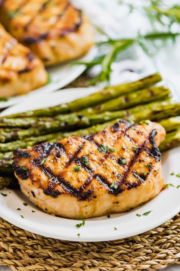 A prok chop on a plate with asparagus.
