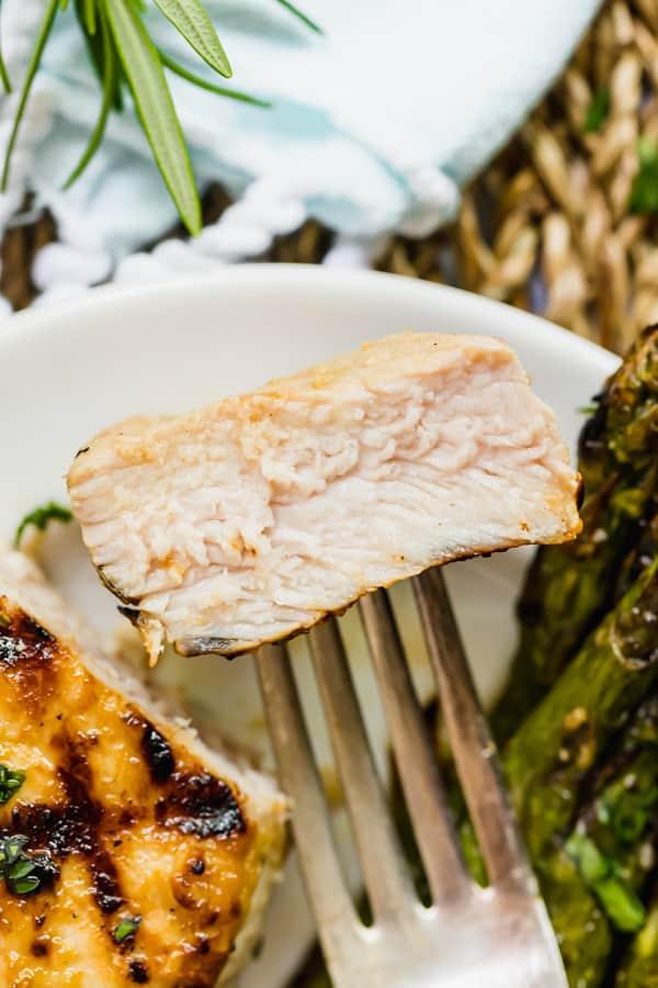 A bite of grilled pork chop on a fork.