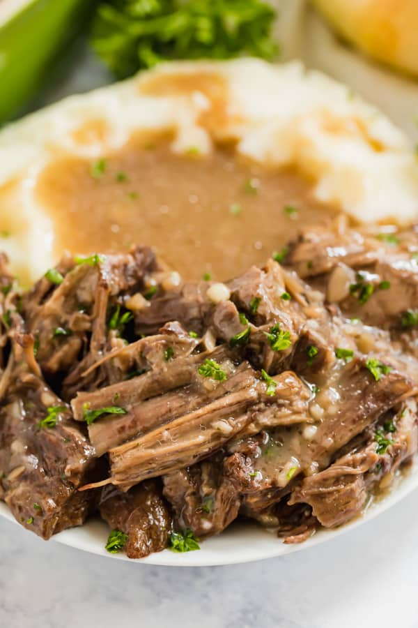 A close up image of slow cooker pot roast with mashed potatoes on a plate.