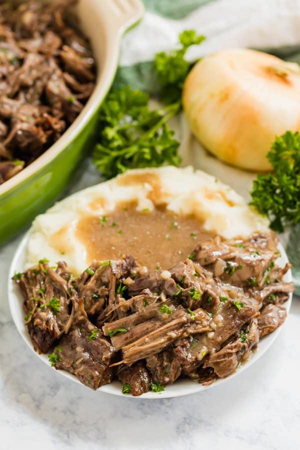 Crock pot roast on a plate with mashed potatoes and gravy.