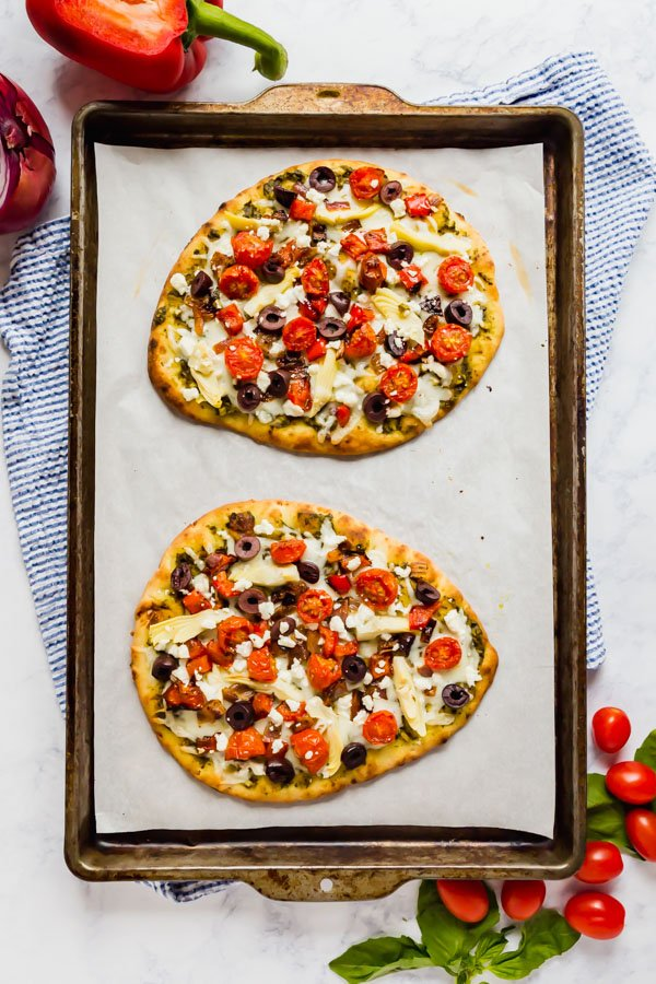 Two flatbreads with roasted veggies on a pan