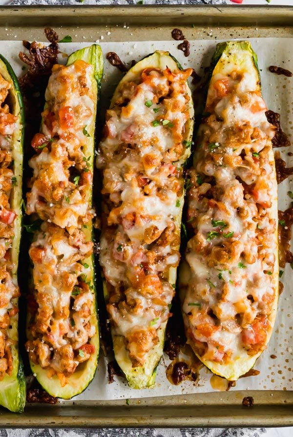 An overhead image of stuffed zucchini on a pan.