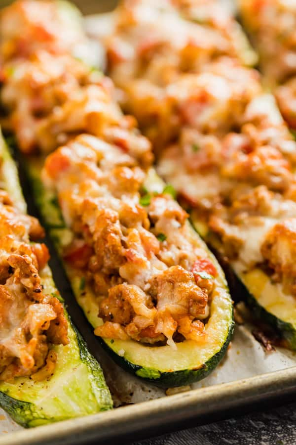 Zucchini boats lined up on a pan.