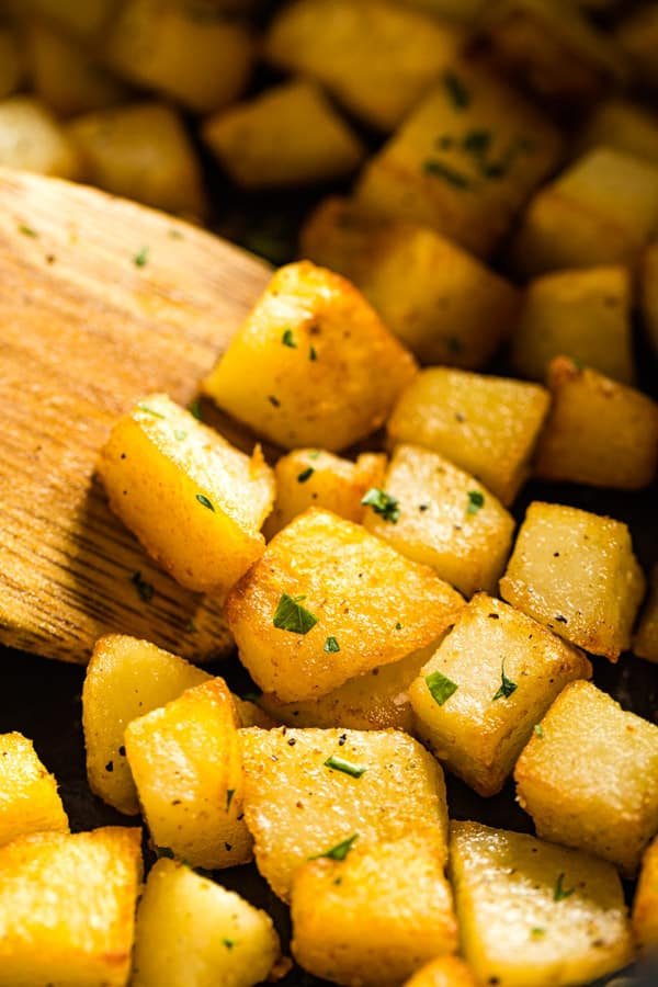A close up of this fried potatoes recipe on a spoon
