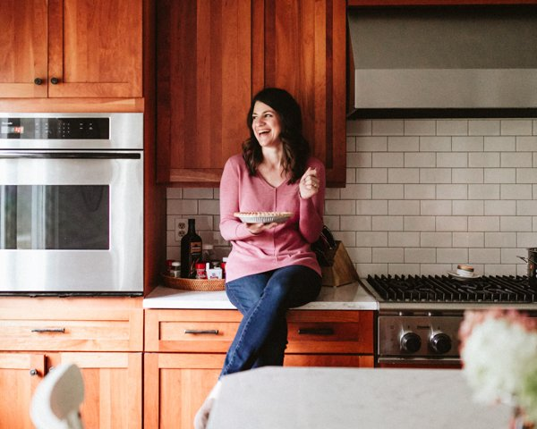A woman sitting on a counter eating pumpkin pie.