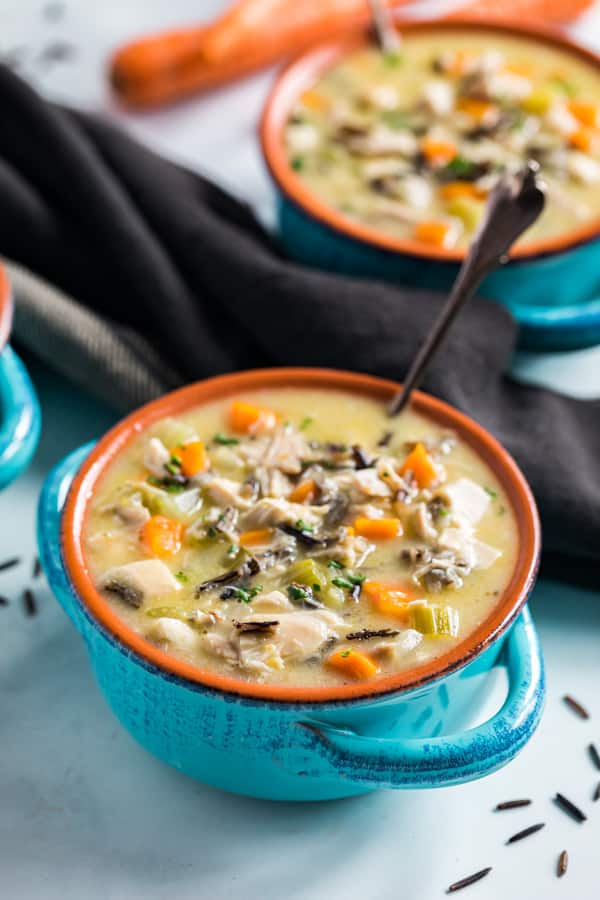 A side shot of a bowl of chicken and wild rice soup with a spoon in it