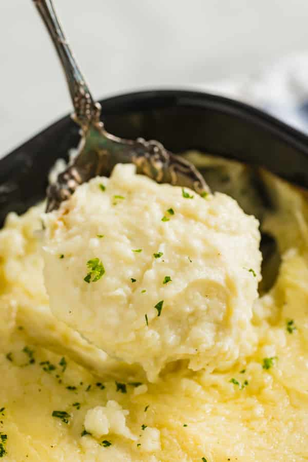 A spoon lifting a scoop of this mashed potatoes recipe.