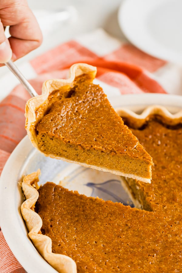 A slice of pumpkin pie being lifted up.