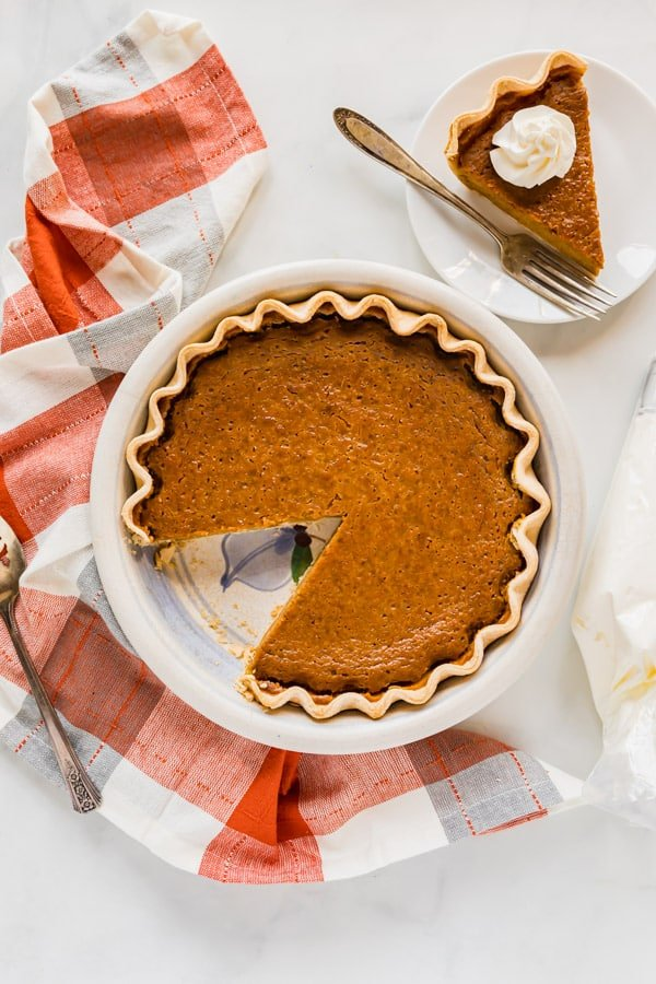 An overhead image of a pumpkin pie with a slice cut out of it!