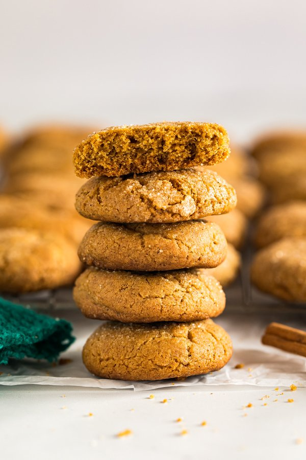 A side angle image of a stack of molasses cookies with the top one broken in half.