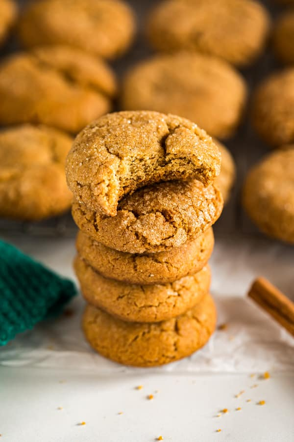 A shot of a stack of molasses cookies with a bite out of the top one.