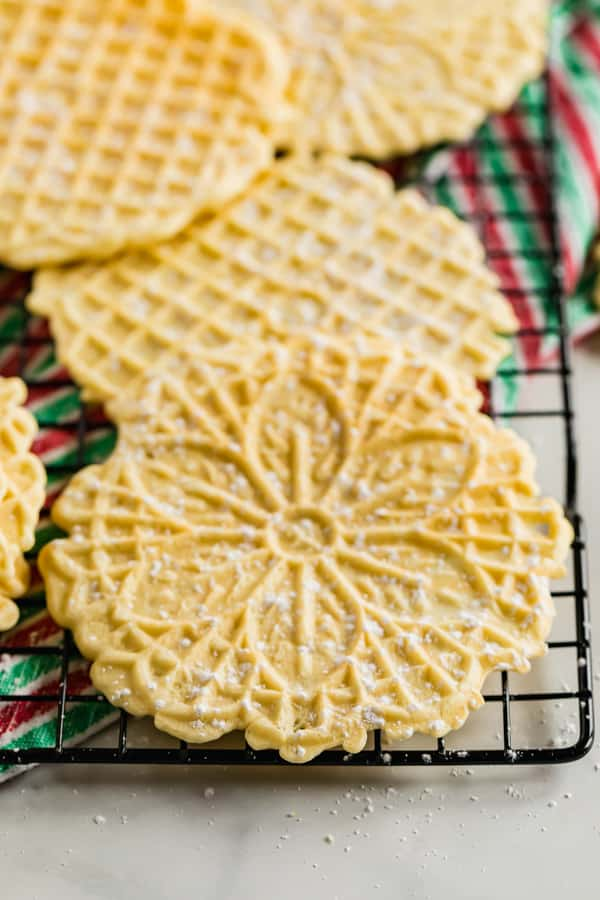 A close up of a pizzelle cookie on a cooling rack.