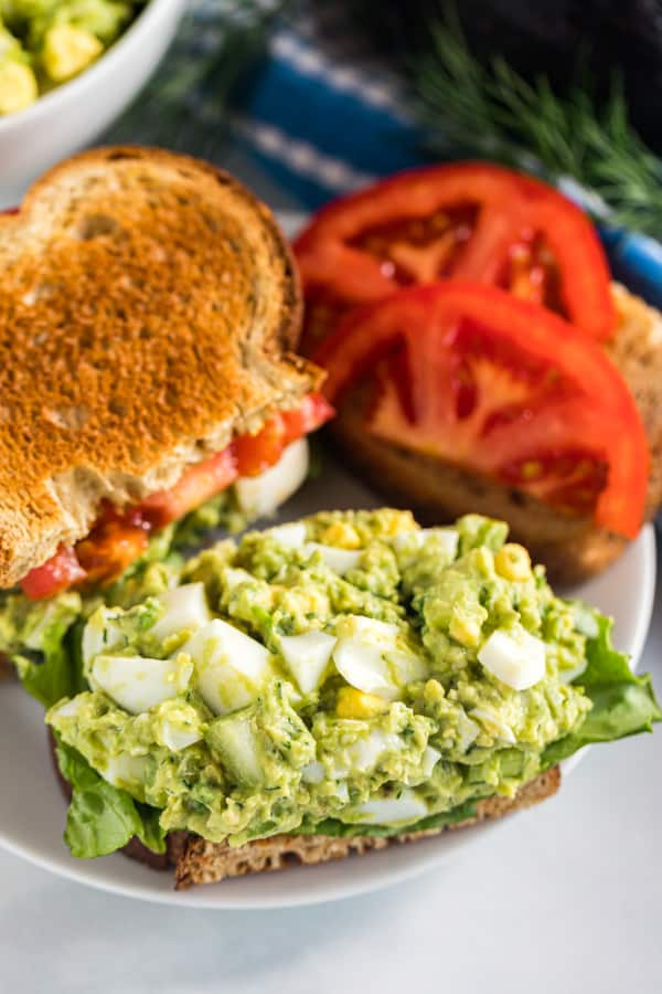 An egg salad sandwich with the top piece of bread pulled off exposing the avocado egg salad