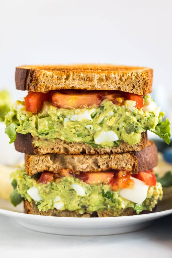 Two halves of avocado egg salad sandwich stacked on top of each other.