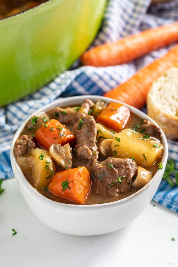 A bowl of lamb stew with a pot behind it