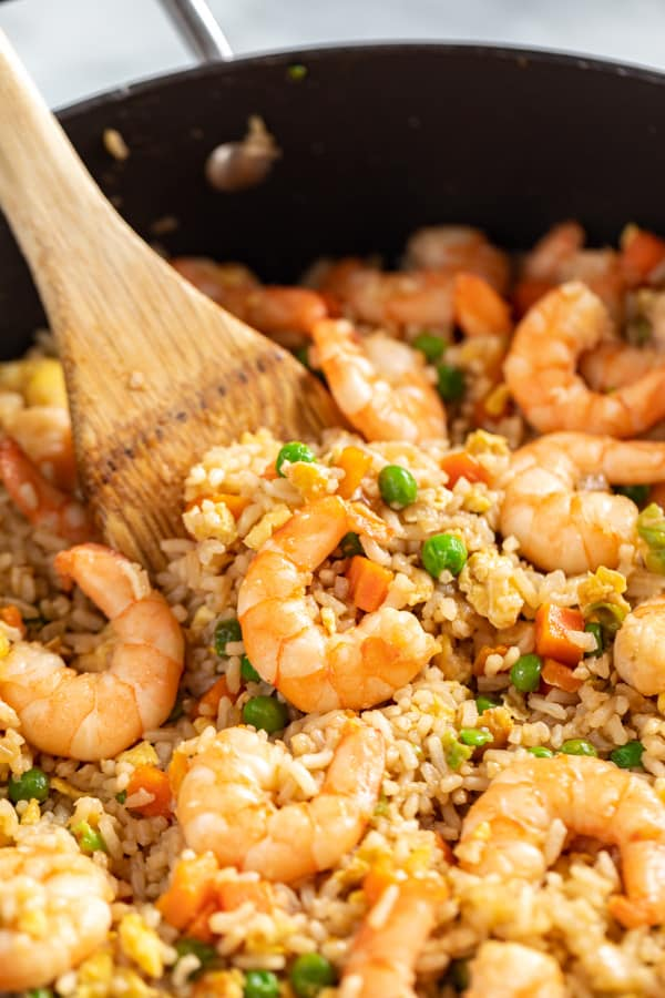 A close up shot of shrimp fried rice in a pan with a spoon.