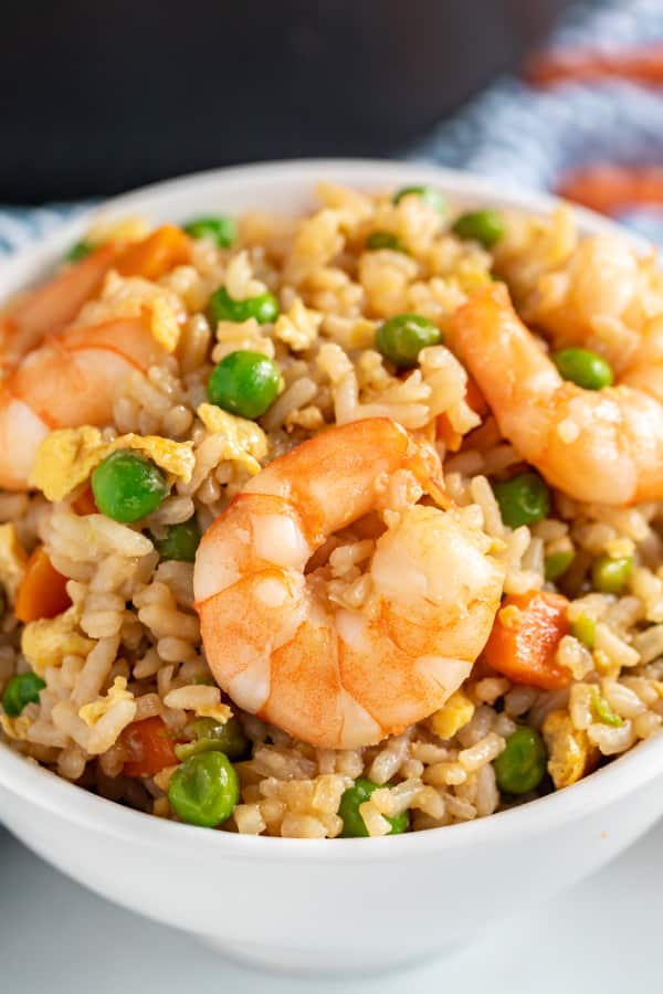 A close up of a shrimp in a bowl of fried rice