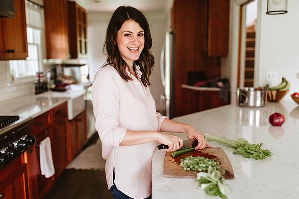 Image of a woman smiling and prepping ingredients