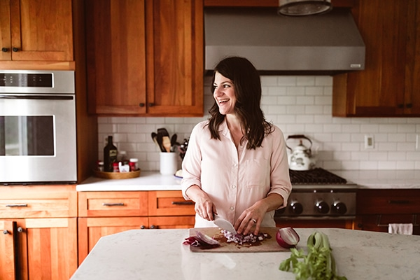 A woman cutting vegetables and smiling.
