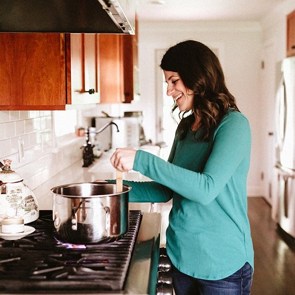 Woman stirring sauce and smiling.