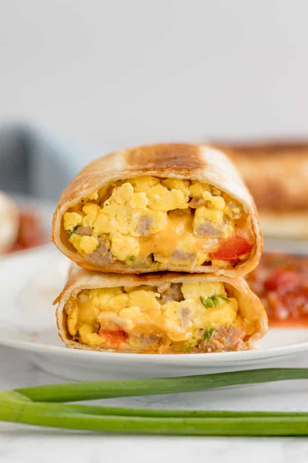 Two halves of a breakfast burrito stacked on tops of each other.