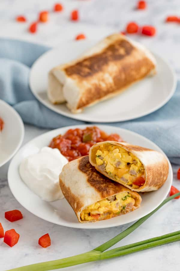 A plate with a breakfast burrito, salsa and sour cream on it.