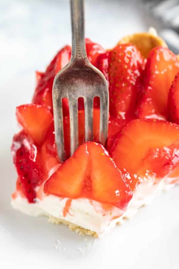 A close up of a fork sticking into the from strawberry on the pie.