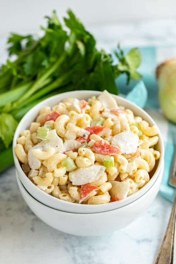 Macaroni salad with crab stacked on another bowl.