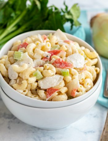 This Crab Macaroni Salad recipe is the perfect way to make a traditional macaroni salad extra special! A creamy, delicious mac salad with crunchy celery, onions and meaty chunks of crab meat (or imitation crab meat). You'll want to make this family favorite again and again!