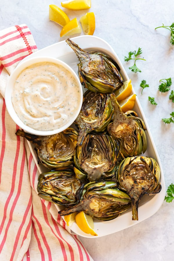 An overhead image of a plate of grilled artichokes with garlic aioli.