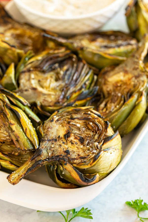 A close up image of the artichoke in the corner of a plate full of them.