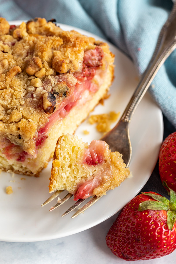 A close up bite of strawberry crumb cake on a fork.