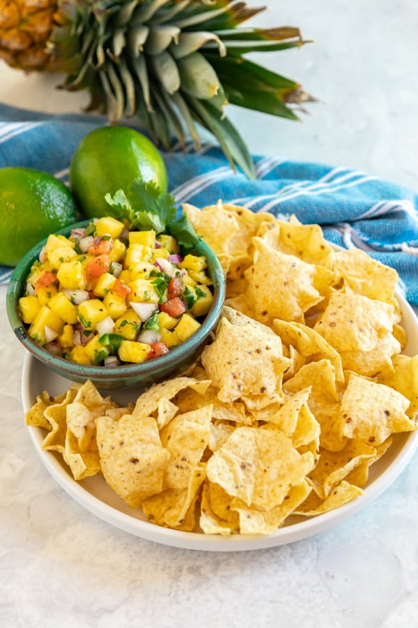 Chips and pineapple salsa with a pineapple and lines in the background.