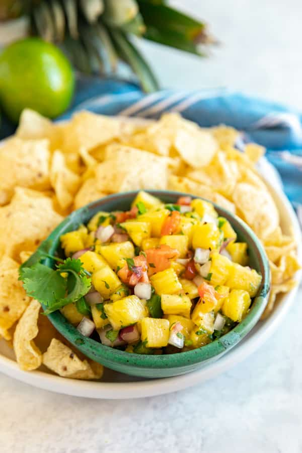 A bowl of pineapple salsa with chips around it.