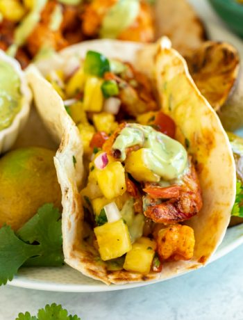 These easy Grilled Shrimp Tacos are about to be your new favorite summertime dinner recipe! Topped with pineapple salsa and an avocado cream sauce, they're quick and easy to make with flavor that will keep you coming back for more.